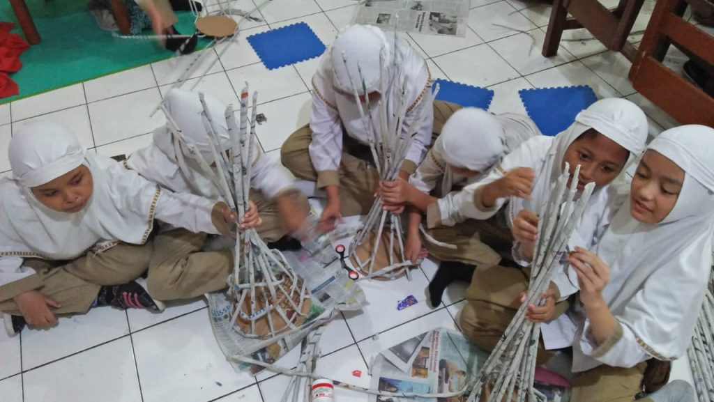 Para siswa kelas 4 SD Muhammadiyah 1 Ketelan Solo asik berkreasi dengan kertas koran bekas, Rabu (06/02/2019).